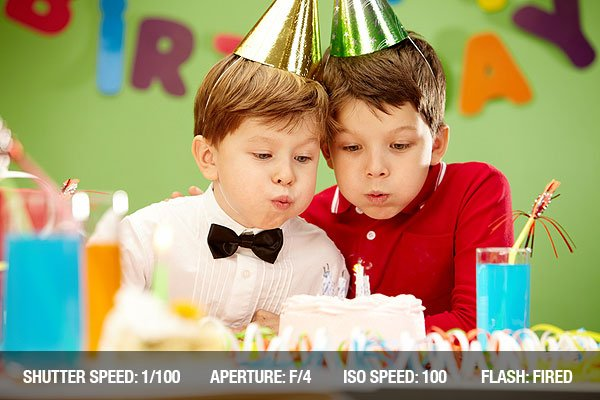 Portrait of happy boys on birthday party blowing at candles on cake
