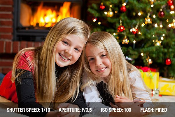 Two girls in front of christmas tree with gifts and fire place