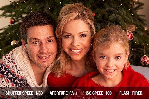 Family Opening Christmas Gifts At Home smiling at camera