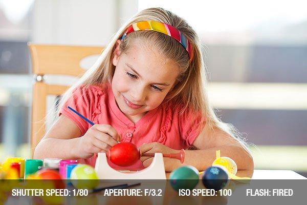 Little girl having fun painting easter eggs