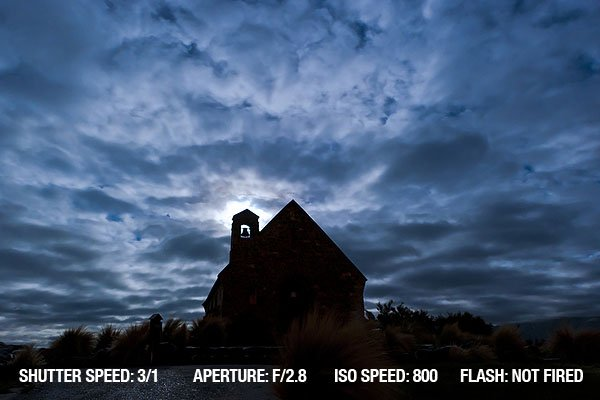An old stone church at Lake Tekapo, New Zealand silhouetted in the moonlight