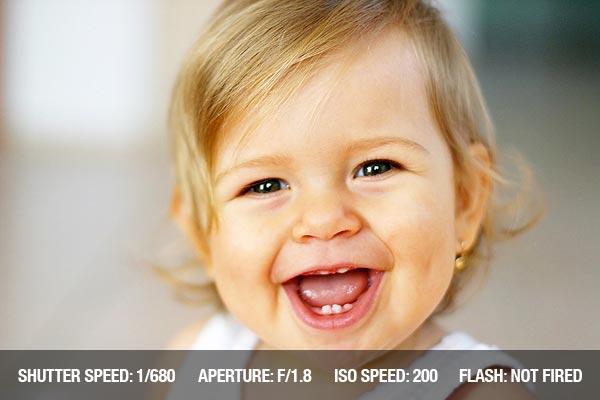 Consejos profesionales fotografía con recien nacidos: Riendo bebé feliz sobre fondo brillante