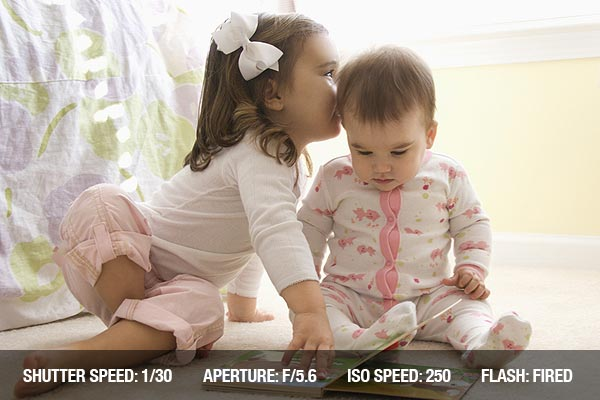 Little girl sitting on bedroom floor looking at book