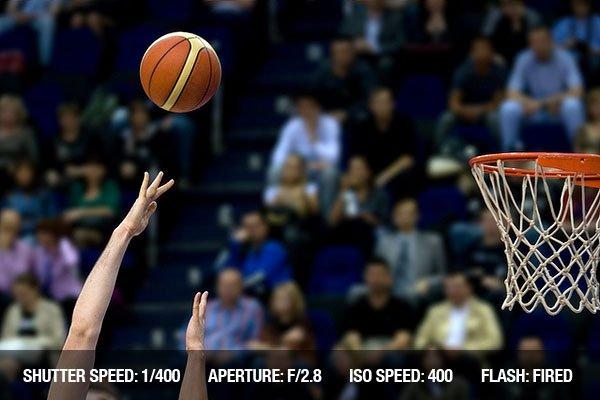 Basketball shooting. Hands of sportsmens plaing basketball in action on full tribune background.