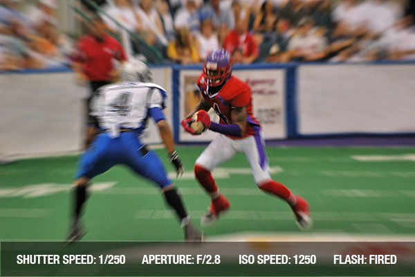 American football action with a player running with ball (zoom motion blur) in a stadium.
