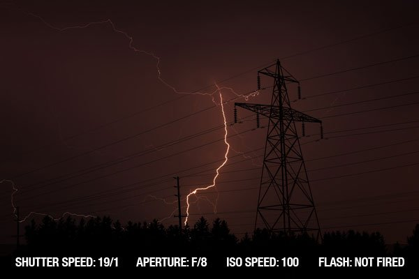 Lightning strike behind trees near a electrical tower