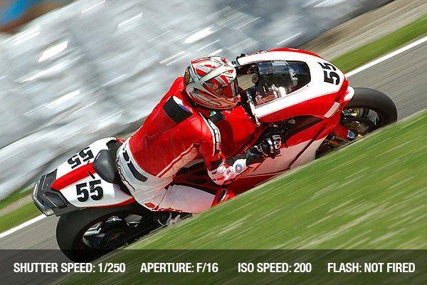 A motorbike racing in circuit, visible panning