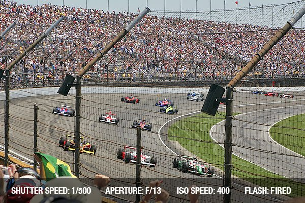 Race cars rounding a turn at the race track, seats filled with cheering fans