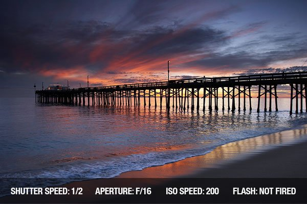 Old wooden pier at sunset with some people walking and fishing