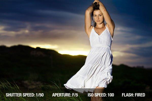Fashion model at sunrise in white dress