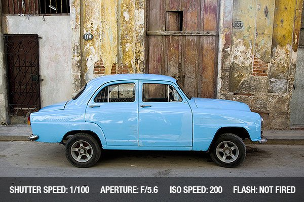Street Photograph of an old car in front of an old house in Havana.