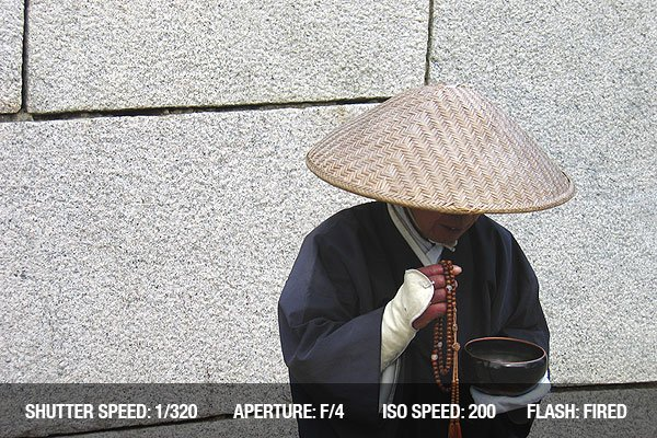 A street performer dressed in traditional Chinese/Japanese peasant costume
