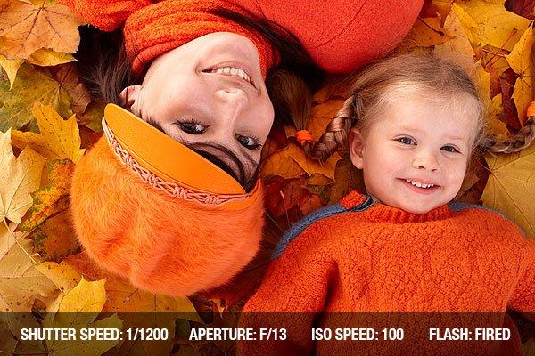 Happy family with child on autumn orange leaf.