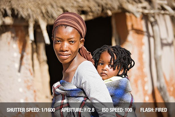 Travel Photography Tip 1 - African mother carry child in a traditional way in front of the hut