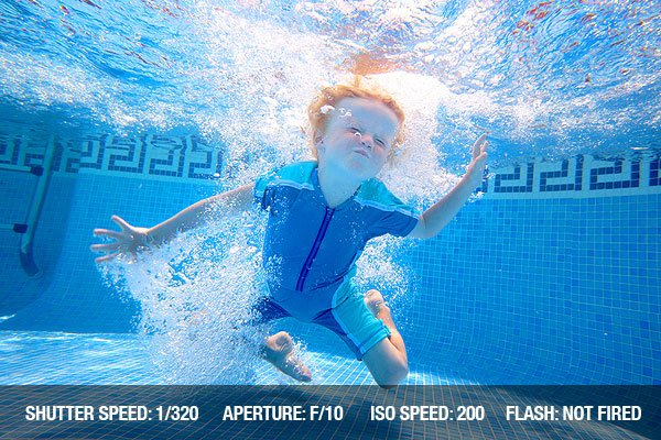Underwater Photography - Young boy holding breath underwater in sunny swimming pool on vacation