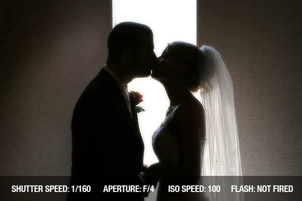 A silhouette photograph of a bride and groom kissing
